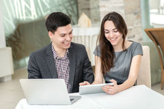 Work and love. Young couple in love sitting at a table in the re Stock Images