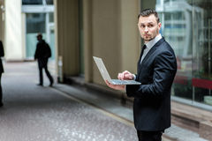 Work at lunch. Successful businessman standing in the street hol Stock Image
