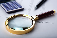 Work with a magnifying glass, a calculator Royalty Free Stock Image