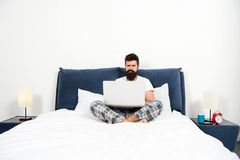 Work that makes him sleepy. bearded man hipster work on laptop. brutal sleepy man in bedroom. mature male with beard in royalty free stock photography