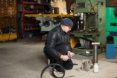 Man in the garage, with flame burning gas welding. Work man is a welder in mask, metal product at home garage, with flame burning gas welding Stock Image