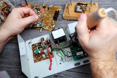 Work of the master on repair of electric equipment, it soldering details. The master on repair of the radio electronic equipment removed the payment scheme from Stock Image