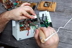 Work of the master on repair of the radio electronic equipment, it is soldering of details and chips. The master on repair of the radio electronic equipment Stock Images
