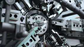 The work of the mechanism of automatic CNC bending machine. Manufacture of a spring of fine wire.  stock video footage