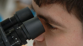 Work with microscope. A scintist works with microscope Stock Photography