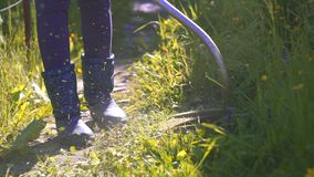 Work mowing grass trimmer close-up. Work mowing grass trimmer close- up slow mo sun stock footage