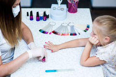 Work in nail studio master with the client child. Royalty Free Stock Photos
