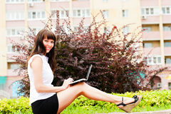 Work with the netbook on the street. Business woman working with netbook Stock Photo