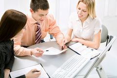 Work at office. Successful businessman and his pretty colleagues working at office Stock Images