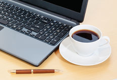 Work office desk with a cup of coffee,  laptop,  pen Royalty Free Stock Image