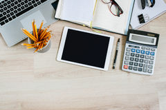 Work office desk table with laptop, tablet, open calendar and calculator. Top view with copy space Royalty Free Stock Images