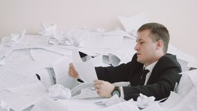 During work, the office worker is experiencing difficulties. A young man in an office suit is busy analyzing papers. A. During work, the office worker is stock footage