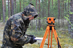 Work with optic level. The device for measurement of levels, is applied in a geodesy, construction, archeology Stock Photo