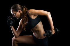 Work out with dumbbells on black background in studio. Dark contrast shot of young beautiful fitness woman with beads of sweat which training in gym. Working out royalty free stock photography