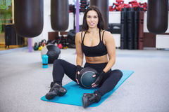 Work out fitness woman exercising with medecine ball in gym smilling and looking at camera. Royalty Free Stock Photos