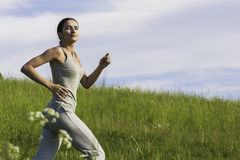Work It Out. Young woman jogging in field Stock Photography