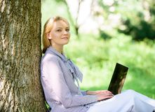 Work outdoors benefits. Woman with laptop work outdoors lean tree. Minute for relax. Girl work with laptop in park sit stock photography