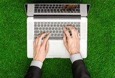 Work outdoors and businessman topic: human hands show the gestures in a black suit and an open notebook on a background of green g Stock Image