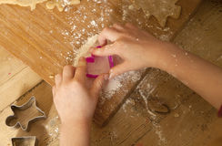 The Work is Over. Now for the play. Little children find something to do with the gingerbread cutters now that the dough has all been used up. By putting flour Royalty Free Stock Image