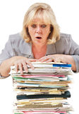 Work overload. Mature woman trying to stop the pile of work from toppling royalty free stock photography