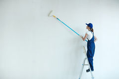 Work with paintroller. Woman with paintroller painting wall of her room Royalty Free Stock Photos