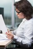 Work with papers. Smart and intelligent woman working with papers at the office royalty free stock photos