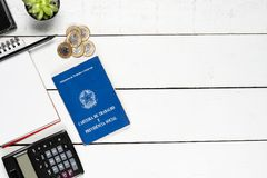 Work permit, cactus, leather notepad, notepad, black pencil, gl. Asses, calculator and some Brazilian one real coins on white background pinus stock images