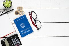 Work permit, cactus, notepad, black pencil, glasses, calculator. And some Brazilian one real coins on white background pinus royalty free stock image