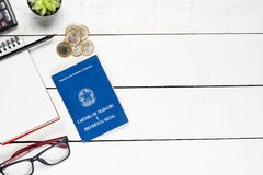 Work permit, cactus, notepad, black pencil,  glasses, calculator. And some Brazilian one real coins on white background pinus Royalty Free Stock Photo
