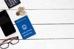 Work permit, calculator, cellphone, glasses and some Brazilian o. Ne real coins on white background pinus Royalty Free Stock Image