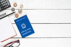 Work permit, calculator, notepad, black pencil, glasses and some. Brazilian  coins on white background pinus Royalty Free Stock Images