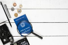 Work permit, camera, calculator, notepad, black pencil, magnifyi. Ng glasses, and some Brazilian coins on white background pinus royalty free stock photography