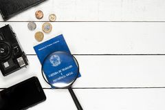 Work permit, cellphone, magnifying glasses, leather notepad, cam. Work permit, cellphone, glasses, leather notepad, camera and some Brazilian coins on white stock image