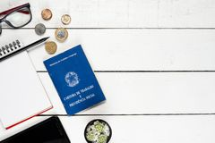 Work permit, notepad, black pencil, cactus, cellphone, glasses a. Nd some Brazilian coins on white background pinus royalty free stock photo