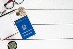 Work permit, notepad, black pencil, glasses, cactus and some Bra. Zilian one real coins on white background pinus Royalty Free Stock Photography