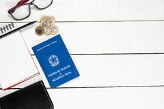 Work permit, notepad, black pencil, leather notepad,  glasses an. D some Brazilian one real coins on white background pinus Royalty Free Stock Images