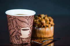 Work place coffee break with Muffin. Styrofoam coffee cup with black coffee and tea spoon with powder banana nut Muffin pastry Stock Image