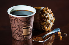 Work place coffee break with muffin. Styrofoam coffee cup with black coffee and tea spoon with powder banana nut Muffin pastry Royalty Free Stock Image