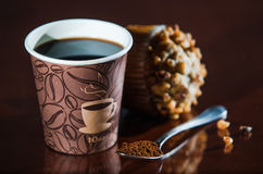 Work place coffee break with Muffin. Styrofoam coffee cup with black coffee and tea spoon with powder banana nut Muffin pastry Royalty Free Stock Photos