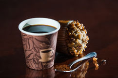 Work place coffee break with Muffin. Styrofoam coffee cup with black coffee and tea spoon with powder banana nut Muffin pastry Royalty Free Stock Images