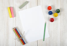 Work place of designer with colored pencils, brush, gouache jars,  chalks and a white paper in top view Stock Image