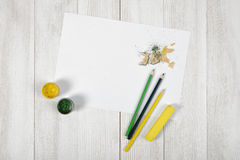 Work place of designer with colored pencils, brush, gouache jars,  chalks and a white paper in top view Royalty Free Stock Photos