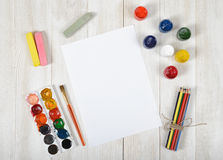 Work place of designer with colored pencils, brush, gouache jars, watercolor paints, chalks and a white paper in top Royalty Free Stock Photo