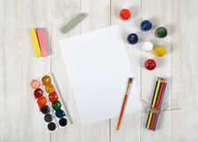 Work place of designer with colored pencils, brush, gouache jars, watercolor paints, chalks and a white paper in top Stock Image