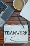 Work place with notebook with note about: Teamwork. Notebook with text inside and some items like notebook pc and coffee Royalty Free Stock Photography