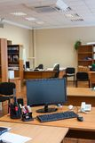 Work place with off lcd monitor of computer, keyboard and mouse are on table in empty room stock image