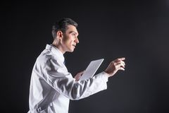 Pleasant handsome scientist using a computer. At work. Pleasant nice handsome scientist holding a tablet and using his computer while being at work Stock Image
