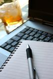Work & Pleasure. Computer keyboard with writing pen and glass drink royalty free stock images