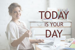 Work with pleasure. Motivational phrase. Portrait of beautiful happy smiling young designer woman sitting at home office desk with cup of coffee, looking at Stock Image