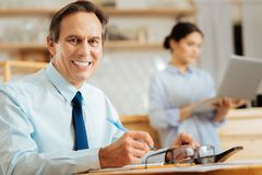 Satisfied busy man smiling and making notices. Royalty Free Stock Images